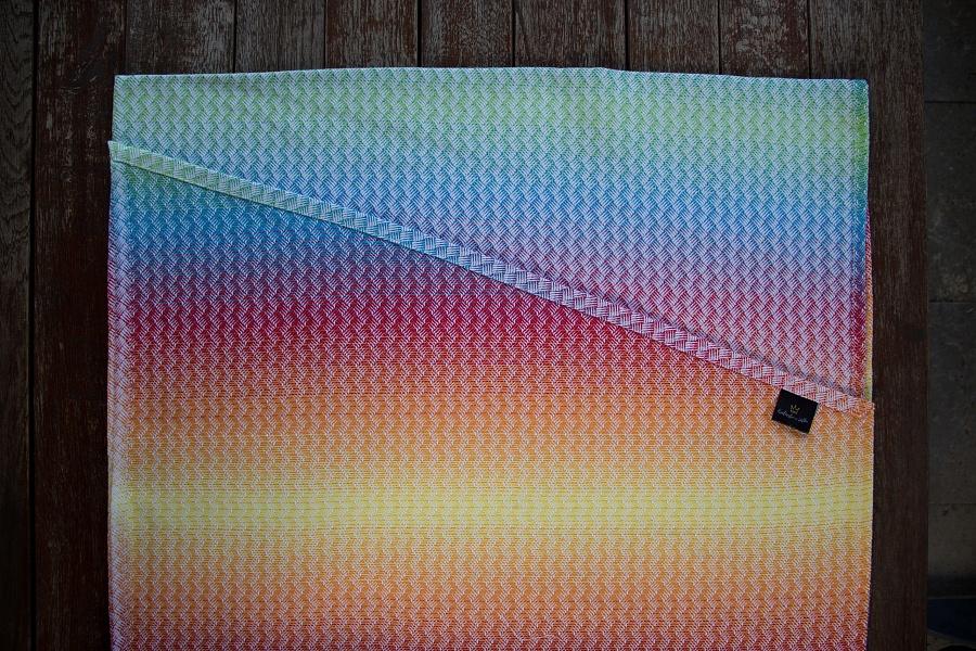 """Nosící šátek """"Ratan"""" na bílé osnově s barevnou duhou"""